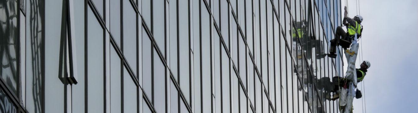 Des techniciens cordistes laveurs de vitre effectuent des travaux en hauteur
