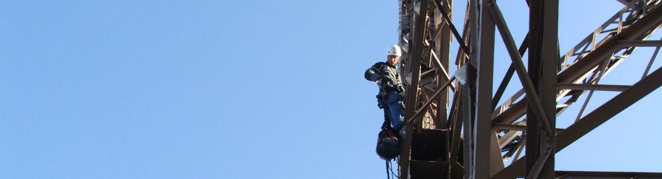 Un cordiste travaille en hauteur à l'aide d'un harnais