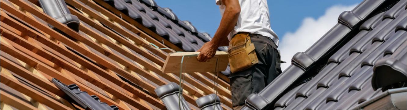 Un couvreur zingueur travaille sur le toit d'un bâtiment