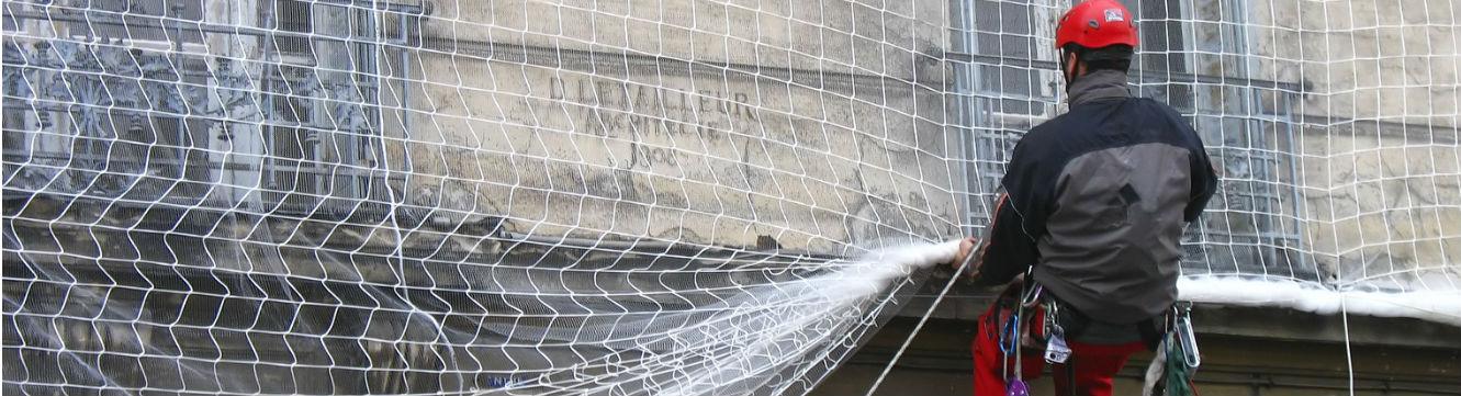 Un Cordiste effectue un travail de protection sur un bâtiment