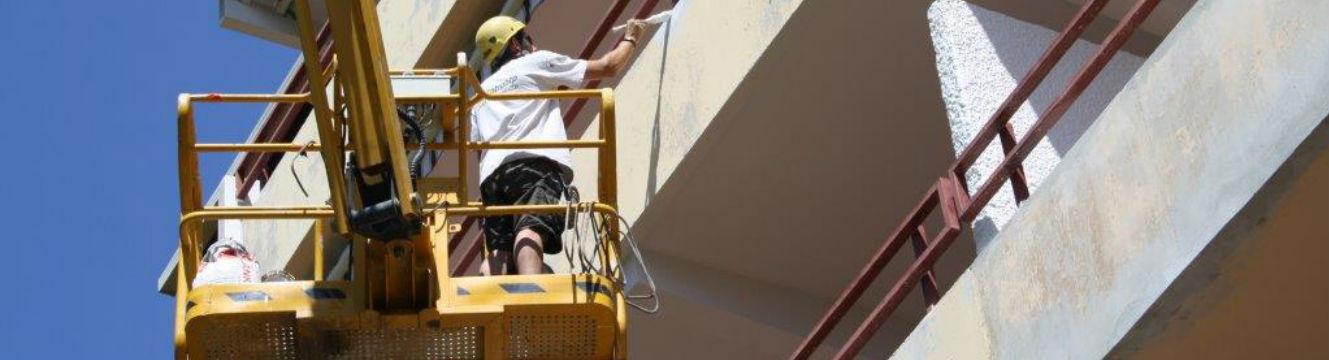 Un technicien cordiste spécialisé bâtiment repeint une façade.