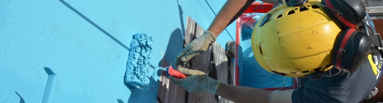 Un cordiste peint une façade en bleu